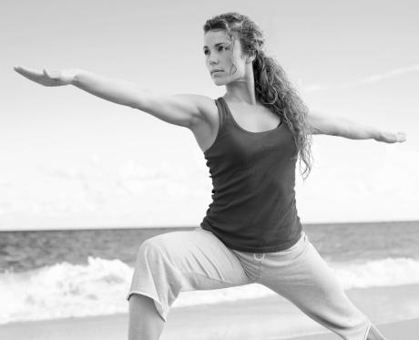 beautiful female doing yoga warrior pose stock photo