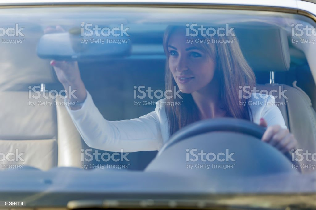 Beautiful female Driver adjusting Mirror - foto de acervo