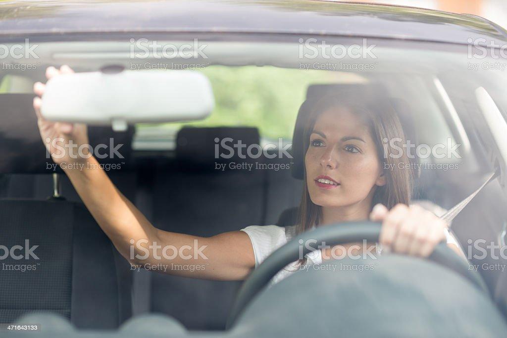 Linda mulher, ajustando o espelho traseira do motorista - foto de acervo