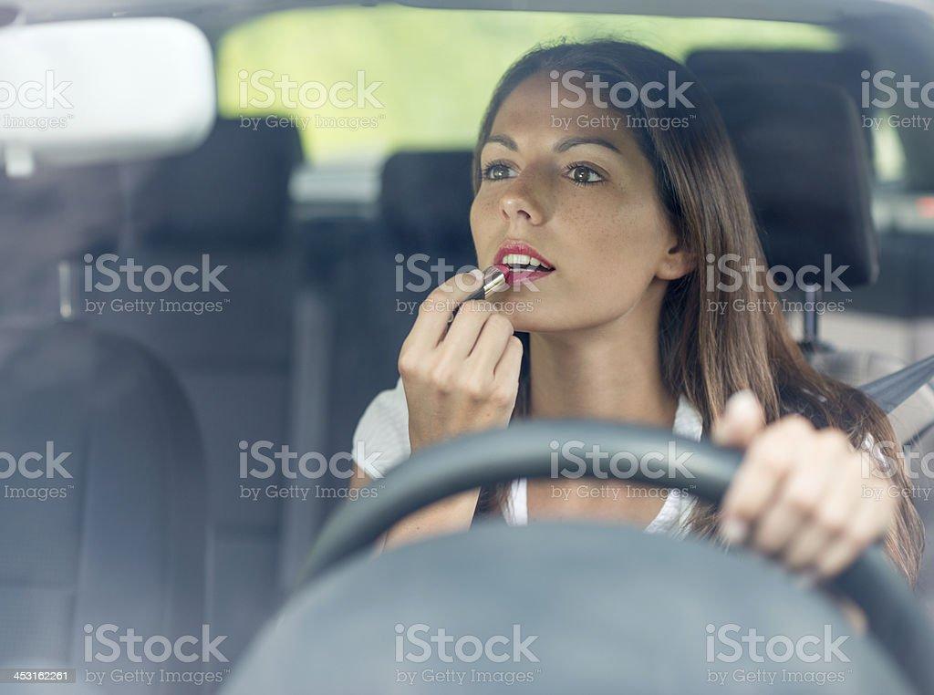 Linda mulher aplicando batom motorista - foto de acervo