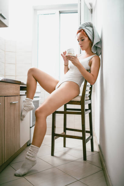 beautiful female eating cakes in kitchen - leotard stock pictures, royalty-free photos & images