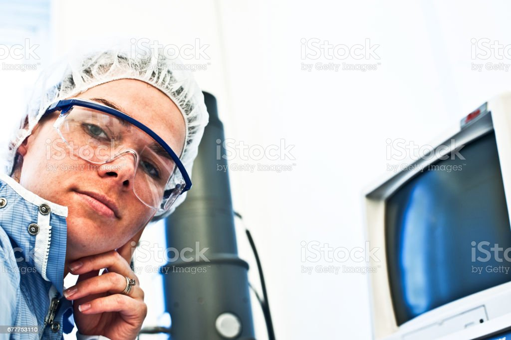 Beautiful Female Engineer (Scientist) Posing With A High Resolution Scanning (Transmission) Electron Microscope In The Lab royalty-free stock photo