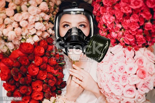 istock Beautiful female enjoying and smelling scent of flowers in gas mask. Allergy protection pharmacy concept. 1132124563
