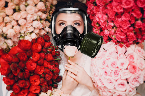 Beautiful female enjoying and smelling scent of flowers in gas mask. Allergy protection pharmacy concept. Beautiful female enjoying and smelling scent of flowers in gas mask. Allergy protection pharmacy concept. antihistamine stock pictures, royalty-free photos & images
