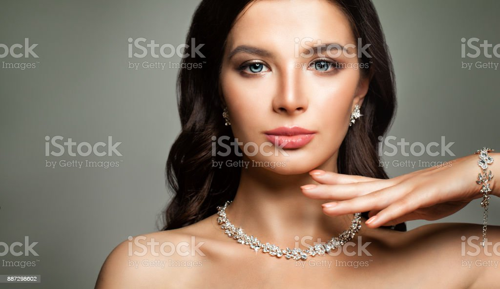 Beautiful Female Face. Young Woman with Perfect Diamond Jewelry stock photo