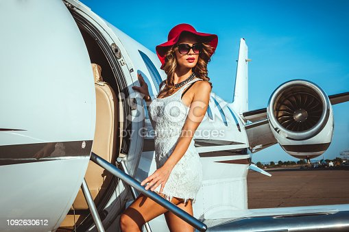 Stunning young female fashion model entering a private plane parked on an airport taxiway. She is looking over her shoulder.