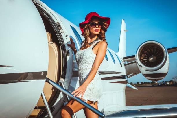 Schöne weibliche Mode-Modell in einem Privatjet auf eine Rollbahn geparkt – Foto