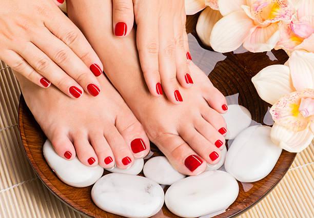 pés femininos bonitos no salão spa no procedimento de pedicure - feet hand imagens e fotografias de stock