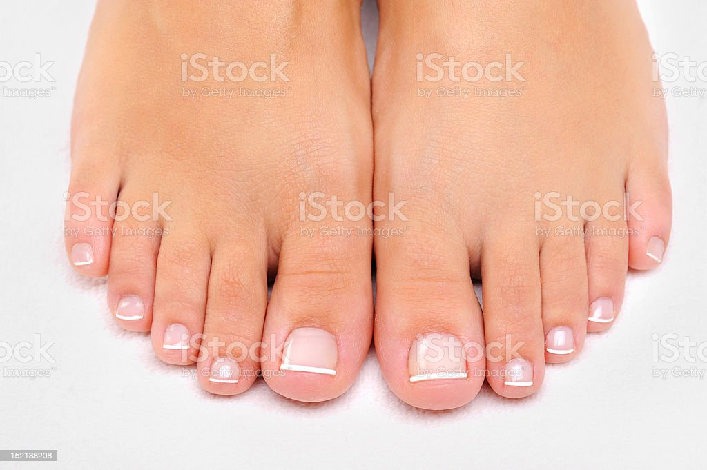 Beautiful female feet with French pedicure closeup stock photo