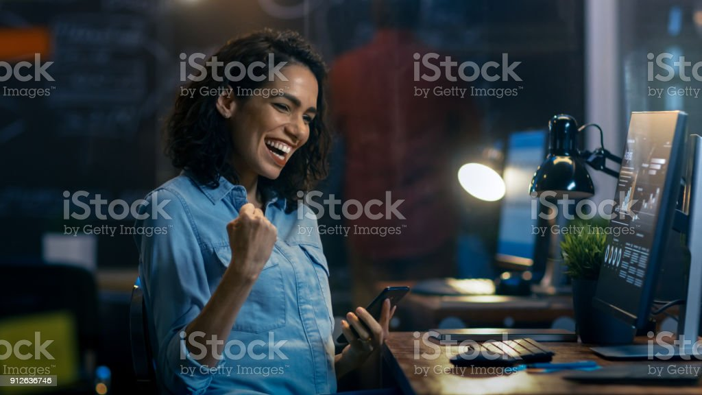 Beautiful Female Financier Uses Mobile Phone, Has Great News and Shows 'Yes' Gesture, Her Personal Computer Showing Graphs and Statistics. She Smiles Charmingly. In the Background Creative Office with Employees. stock photo