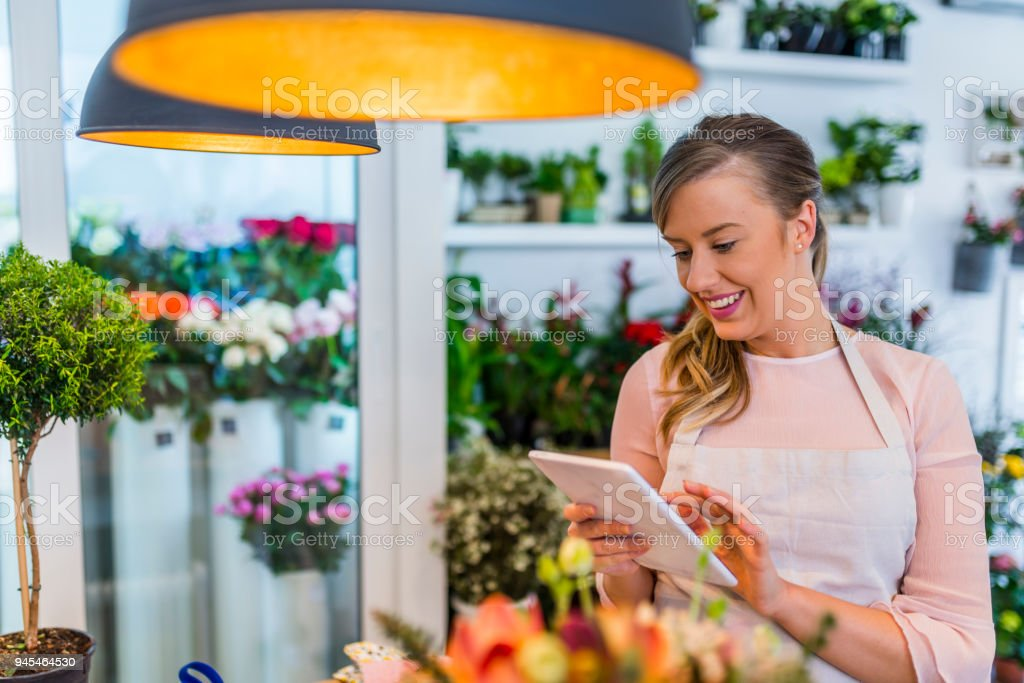 Young owner of flower shop taking orders online by tablet. Small...