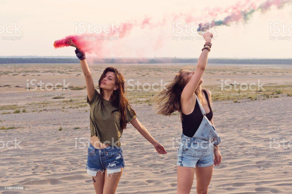 Beautiful female friends holding distress flares Beautiful female friends holding distress flares at desert. Young women are enjoying together during vacation. Hipsters are hiking and having fun on sand. 20-24 Years Stock Photo