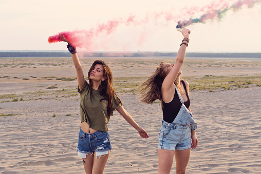 Beautiful Female Friends Holding Distress Flares Stock Photo - Download Image Now
