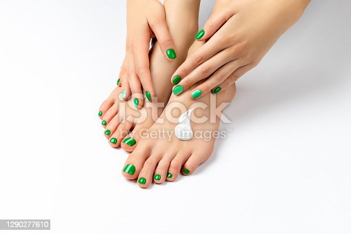 istock Beautiful female hand apply cream on her foot 1290277610
