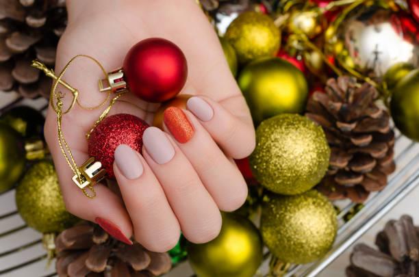 schöne weibliche hand mit weihnachten nageldesign - nageldesign weihnachten stock-fotos und bilder