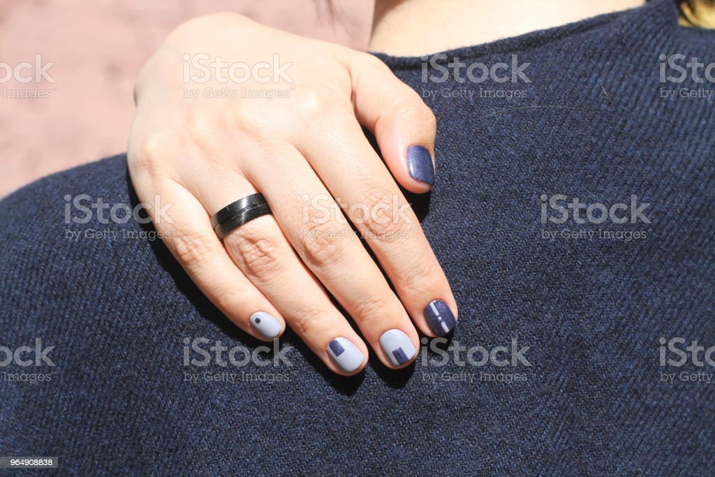 Beautiful female hand with extraordinary manicure. Creative nail design in blue. Ultra stylish colors of nail polish. royalty-free stock photo