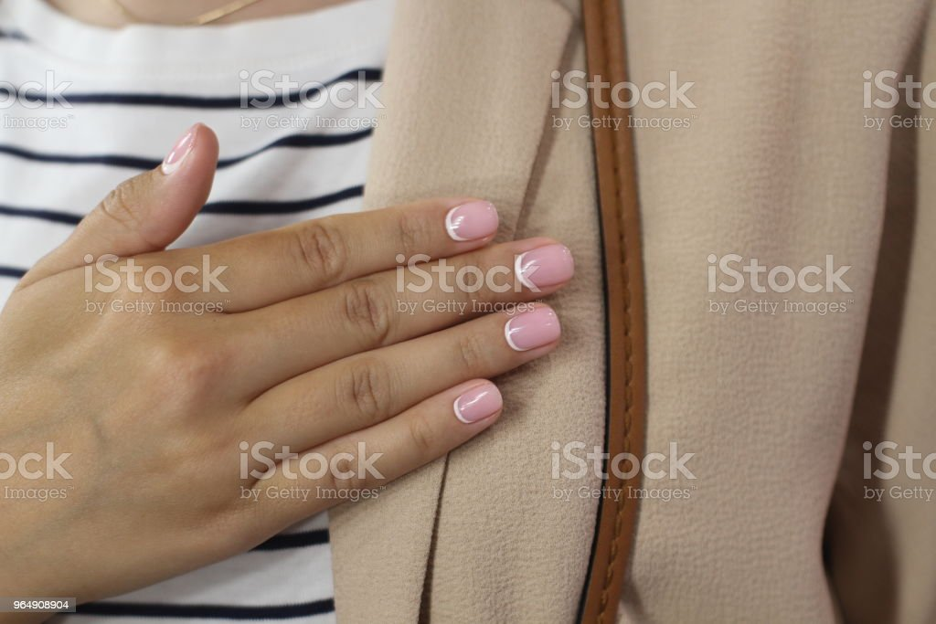 Beautiful female hand with manicure. Delicate pink nail polish with white crescentsand and well conditioned fingers. royalty-free stock photo
