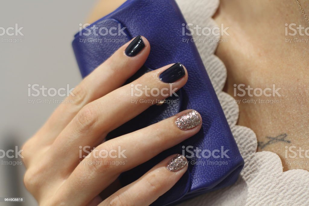 Beautiful female hand with manicure holds blue leather wallet. Dark blue and brilliant silver nail polish. - Royalty-free Adult Stock Photo