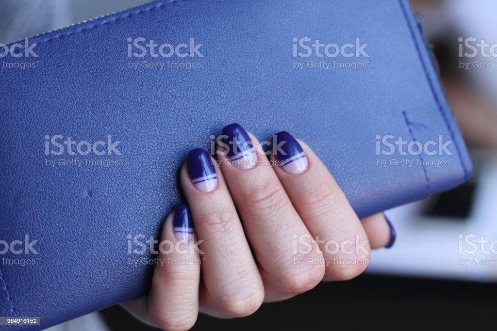 Beautiful female hand with manicure holds leather clutch. Dark blue nail polish with creative design. royalty-free stock photo