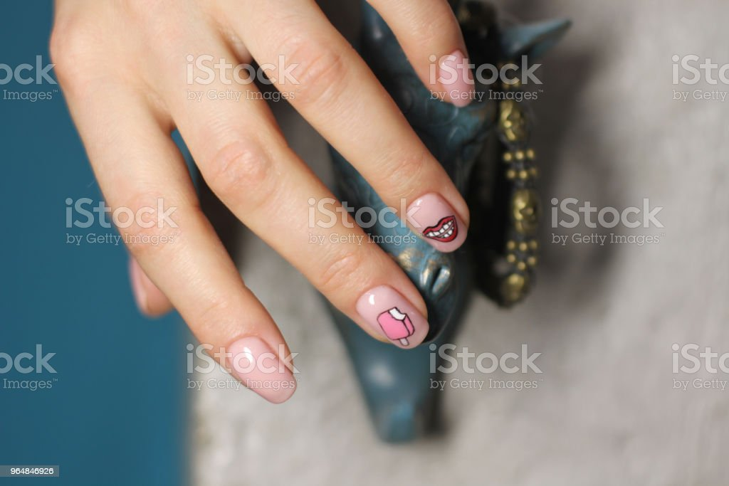 Beautiful female hand with manicure. Light pink nail polish with creative design. Lips and ice cream stickers. royalty-free stock photo