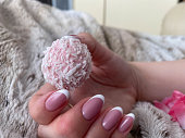 istock A beautiful female hand with pink nails and manicure is holding a beautiful pink delicious sweet candy 1327701418