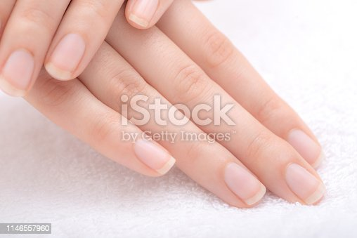 Beautiful female hands and nails on white towel.