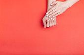 赤い背景に古典的なマットマニキュアと美しい女性の手