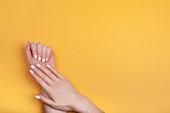 黄色の背景に古典的なマットマニキュアと美しい女性の手