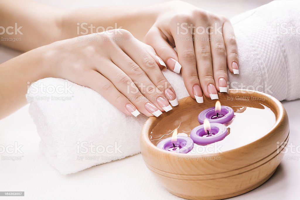 beautiful female hands with aromatic candles and towel. Spa royalty-free stock photo