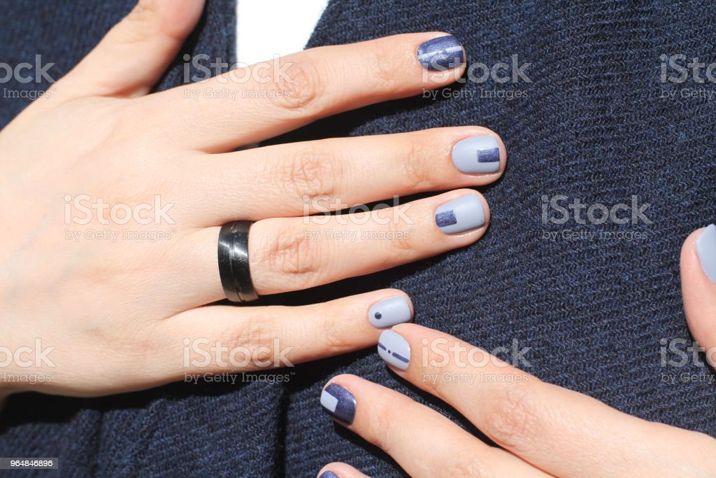 Beautiful female hands with extraordinary manicure. Creative nail design in blue. Ultra stylish colors of nail polish. royalty-free stock photo