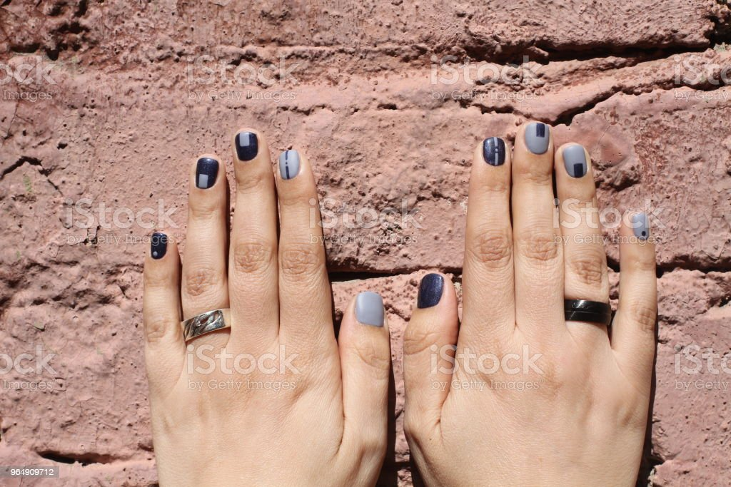 Beautiful female hands with extraordinary manicure on a brick wall. Creative nail design in blue. Ultra stylish colors of nail polish. royalty-free stock photo