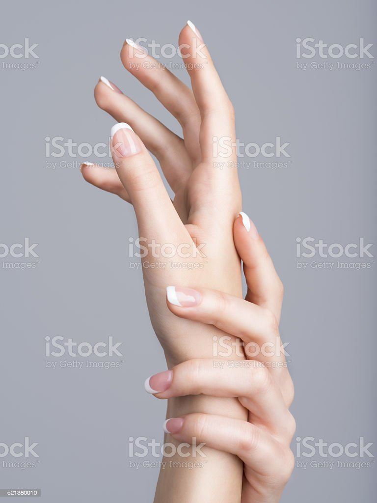 Beautiful female hands with french manicure on nails stock photo