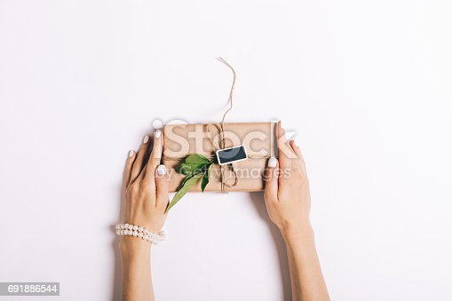 istock Beautiful female hands with manicure holding a box with a gift on a white table 691886544