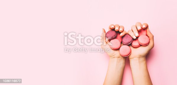 istock Beautiful female hands with trendy manicure holding pink macaroon cake. 1036116572
