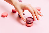 トレンディなマニキュアのピンクのマカロン ケーキを保持するいると美しい女性の手。