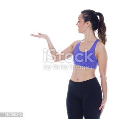 istock Beautiful female in sports clothing is presenting / showing to her side 1080299240
