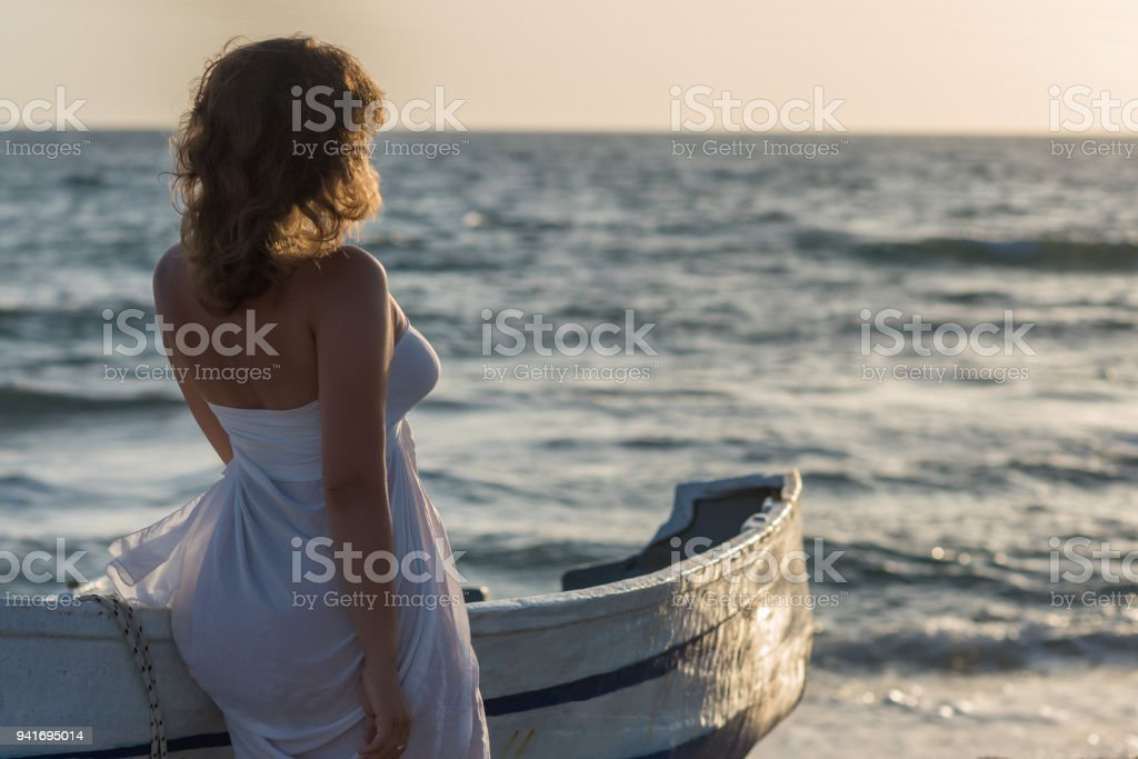 Beautiful female in the pareo near boat on the sand stock photo