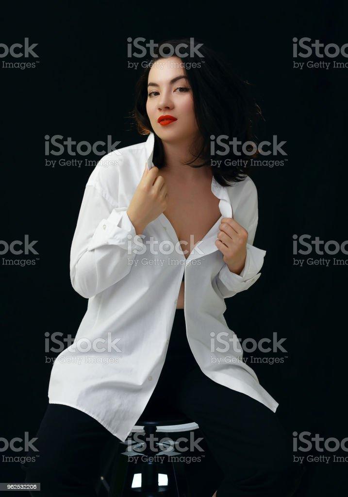 Linda mulher na camisa branca, sentado na cadeira. Retrato em fundo preto. - Foto de stock de Adulto royalty-free