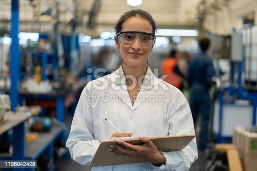 Beautiful female internal auditor at a manufacturing plant smiling at camera while holding a clipboard and wearing protective goggles