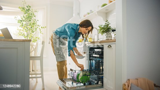 istock Beautiful Female is Loading Dirty Plates into a Dishwasher Machine in a Bright Sunny Kitchen. Girl in Wearing an Apron. Young Housewife Uses Modern Appliance to Keep the Home Clean. 1248942280
