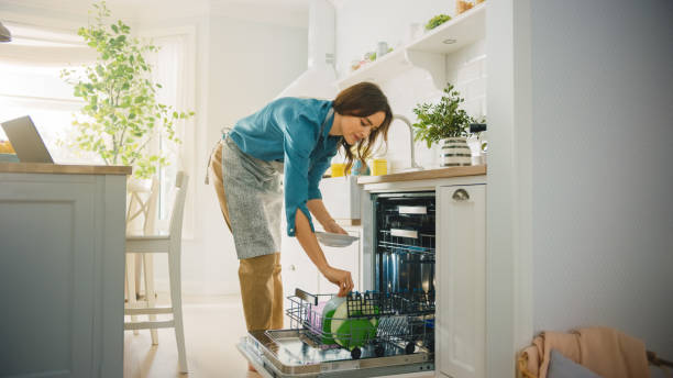 Beautiful Female is Loading Dirty Plates into a Dishwasher Machine in a Bright Sunny Kitchen. Girl in Wearing an Apron. Young Housewife Uses Modern Appliance to Keep the Home Clean. stock photo
