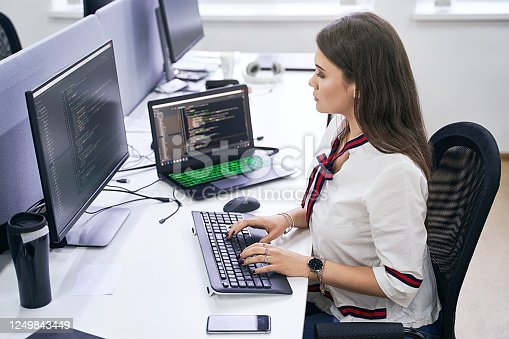 Beautiful young woman working on computer in IT office, sitting at desk and coding, working on a project in software development company or technology startup.