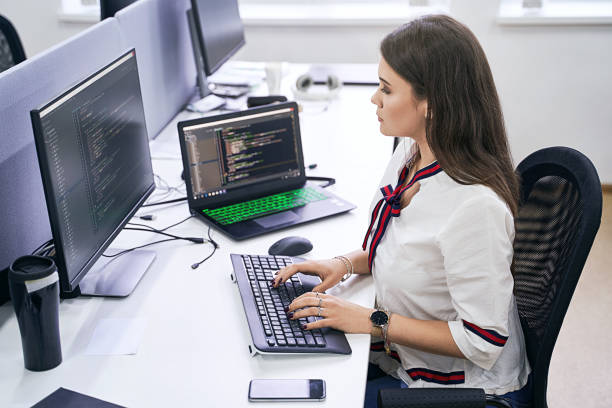 Beautiful female junior software developer working on computer in IT office, sitting at desk and coding, working on a project in software development company or technology startup. High quality image. stock photo
