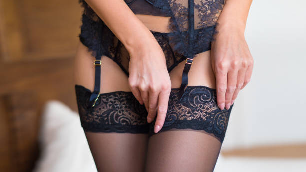 Beautiful female legs in black stockings with garter in a bedroom interior Beautiful female legs in black stockings with garter in a bedroom interior. lingerie stock pictures, royalty-free photos & images
