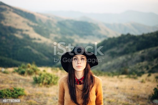 Beautiful female tourist in the sweater looking at camera and standing at the beautiful mountain scenery