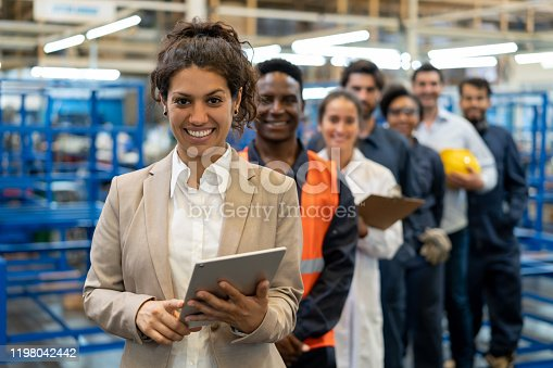 Beautiful female manager at a factory holding a tablet and team of blue collar workers, engineers and inspectors standing in a row smiling at camera very cheerfully