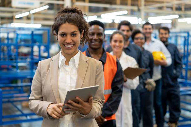 schöne weibliche managerin in einer fabrik, die ein tablet und ein team von arbeitern, ingenieuren und inspektoren hält, die in einer reihe stehen und vor der kamera lächeln - berufliche beschäftigung stock-fotos und bilder