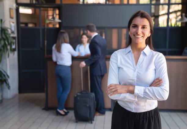 piękna kobieta kierownik luksusowego hotelu stoi kamery uśmiechając się z rękami skrzyżowanymi - hotel zdjęcia i obrazy z banku zdjęć