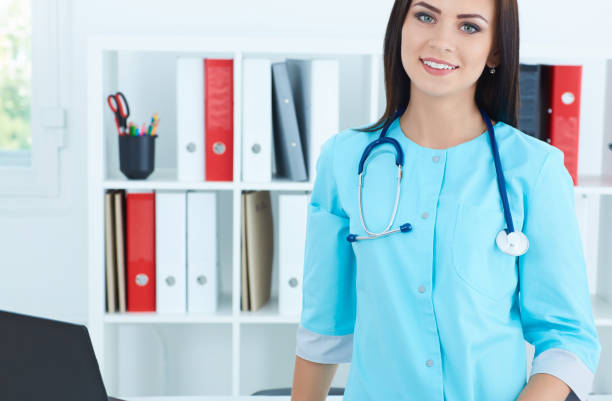 Beautiful female medicine doctor standing in her office  looking in camera. Medical help or insurance concept. stock photo