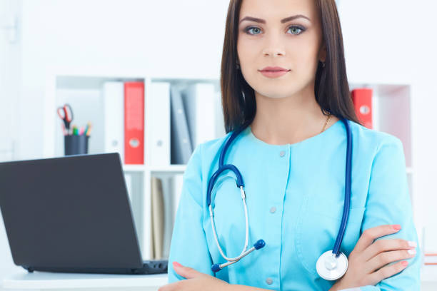 Beautiful female medicine doctor standing in her office with hands crossed on her chest. Medical help or insurance concept. Doctor is waiting for patient to examine. stock photo